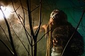 foto of werewolf  - Muscular man with skin and dreadlocks looking at a bright light source - JPG