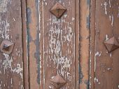 foto of stud  - Detail of an old weathered door with peeling paint and metal studs