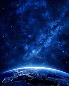 stock photo of planet earth  - Earth at night as seen from space with blue glowing atmosphere and space at the top - JPG