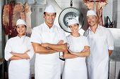foto of slaughterhouse  - Portrait of confident male butcher with colleagues standing in butchery - JPG