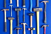 pic of carpentry  - World of hammers with a large assortment of different shapes arranged neatly in vertical lines on a bright blue background in a DIY carpentry building maintenance and renovation concept - JPG