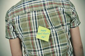 stock photo of prank  - a young caucasian man wearing a plaid patterned shirt with a yellow sticky note attached to his back with the text happy april fools day written in it - JPG