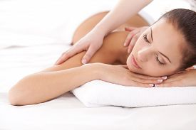 stock photo of therapist  - Beautiful young woman lying on front and looking at camera while massage therapist massaging her shoulders - JPG