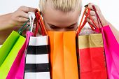 picture of antidepressant  - Blond woman inspecting content of colored paper bags with fresh buyings - JPG