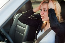 stock photo of panic  - Scared young student girl panic in a car - JPG