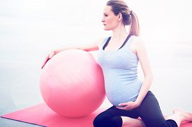 foto of pregnancy exercises  - Pregnant woman doing pilates exercises to keep fit and tone her muscles sitting on a gym mat with a pilates ball looking to the side while supporting her swollen belly with her hand - JPG