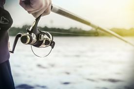foto of rod  - hand holding a fishing rod with reel - JPG