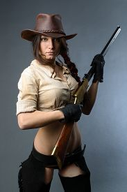 pic of cowgirl  - Beautiful cowgirl with gun on gray background - JPG