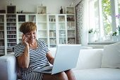 Senior woman talking on mobile phone while using laptop in living room at home poster
