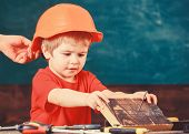 Toddler In Protective Helmet At Workshop. Child Cute And Adorable Play With Wood And Screw While Mal poster