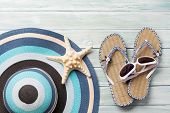 Travel vacation background concept with beach hat, sunglasses, flip flops and starfish on wooden bac poster