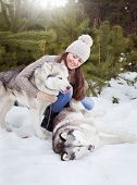 Beautiful, Cheerful Girl In The Winter Forest With Two Dogs Huskies. poster
