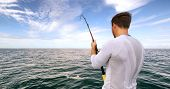 Shark fishing activity on fisherman boat in Florida. Travel tourist man catch and release of spinner poster