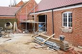 Building Site In Uk With Brick House Extension Under Construction poster