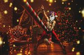 Bad Santa concept. Portrait of a nude tattooed Santa with purple dreads demonstrating antisocial beh poster