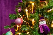 Christmas Tree Decorated In A Purple Theme With A Prominent Purple Snowman And Decorative Purple Bal poster