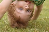 foto of fidget  - happy little boy stand on head on the summer lawn - JPG