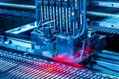 Electronic circuit under surface-mounting machine. Shot in blue toning filter. Surface-mount technol poster