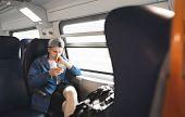 Portrait Of A Focused Guy Sitting In A Train Near The Window, Traveling And Using A Smartphone. Trip poster