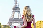 Woman At Eiffel Tower Paris, France. Young Tourist Girl In A Red Romantic Dress Admiring The Views.  poster
