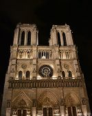 Notre Dame Cathedral At Midnight. Facade, Towers, Rose Window, Archs And Statues. Paris, France. poster