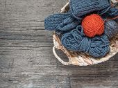 The Orange Ball Of Wool Yarn And Blue Yarn In A Wicker Basket On A Wooden Background. Flat Lay, Top poster