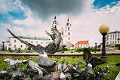 Minsk, Belarus. Doves Pigeons Flying Near Cathedral Of Holy Spirit And Monastery Of Holy Spirit Bazi poster