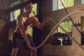 Fit, sporty and athletic sportsman working in a gym. Man training using battle ropes. Cross fit, spo poster