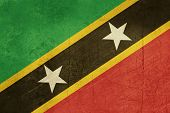 Grunge sovereign state flag of country of Saint Kitts and Nevis in official colors. round
