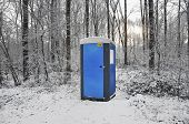 stock photo of porta-potties  - Blue mobile toilet cabin in a snow covered forest - JPG