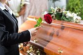 stock photo of coffin  - Mourning woman on funeral with red rose standing at casket or coffin - JPG