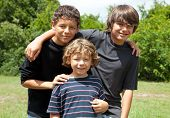 Three adorable boys, two adolescent friends and one little brother smiling. Diversity.   The two bro