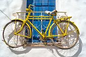 pic of greek-island  - Decorative bicycle hanging from a window in a Greek house on Naxos island Greece - JPG
