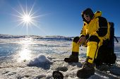 stock photo of ice fishing  - Fisherman enjoying a day on the ice on a bright sunny day - JPG