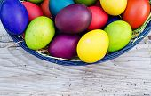 stock photo of chicken  - Colorful Easter eggs in basket on wooden background - JPG
