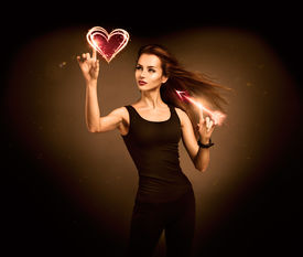 stock photo of heartbreaking  - Sexy Woman Aiming to the Glowing Heart with an Arrow on Dark Background - JPG