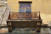 stock photo of neoclassical  - Winged female figure rusty floral pattern and swans on balcony balustrade of abandoned neoclassical house - JPG