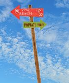 stock photo of nudism  - wooden arrow direction signs post to the nude and private beach against a blue sky - JPG
