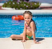 stock photo of lifeline  - smiling cute little girl swims with a lifeline in the pool - JPG