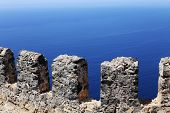 foto of old stone fence  - stone fence on a background of the blue sea - JPG