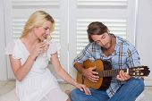 stock photo of serenade  - Handsome man serenading his girlfriend with guitar at home in the living room - JPG