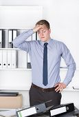 pic of horrifying  - Young despaired businessman is standing in front of many files on his desk in the office - JPG