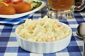 stock photo of potato-field  - A bowl of potato salad on a picnic table with beer and corn dogs  - JPG