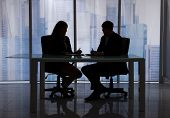 image of late 20s  - Silhouette businessman and businesswoman discussing at desk in office - JPG