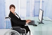 foto of handicap  - Side view portrait of handicapped businesswoman using computer while sitting on wheelchair in office - JPG
