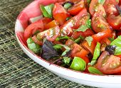 foto of plum tomato  - Summer salad with plum baby tomato greek purple lime and genovese basil in country style red gingham plate