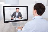 pic of video chat  - Rear view of businessman video conferencing with coworker on desktop PC at office desk - JPG