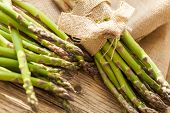 stock photo of bundle  - Fresh healthy green asparagus spears tied in bundles on a rustic wood surface on display at a farmers market for cooking a delicious appetizer or vegetable accompaniment to a meal - JPG