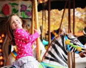 stock photo of carnival ride  - a young girl riding on a merry go round at the zoo - JPG