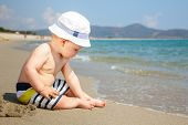 picture of little boys only  - Baby boy wearing hat and shorts playing on a beach - JPG